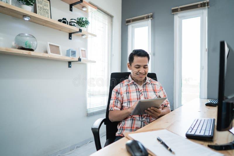 Entrepreneur détendant utilisant le comprimé à son bureau photos libres de droits