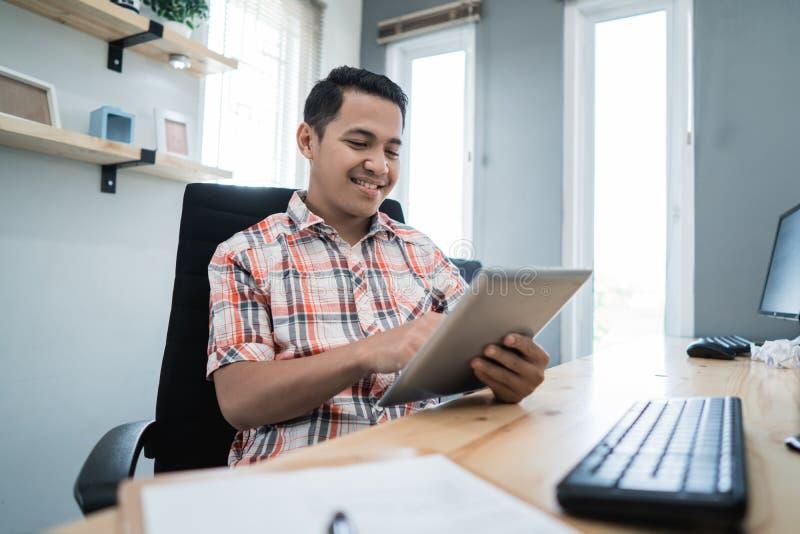 Entrepreneur détendant utilisant le comprimé à son bureau images stock