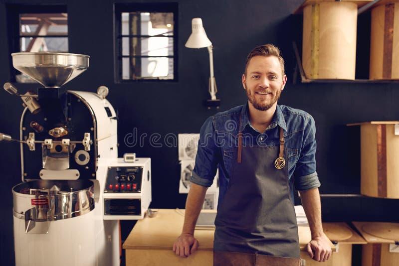 Entrepreneur dans sa station thermale moderne de roastrery et de distribution de café photo stock