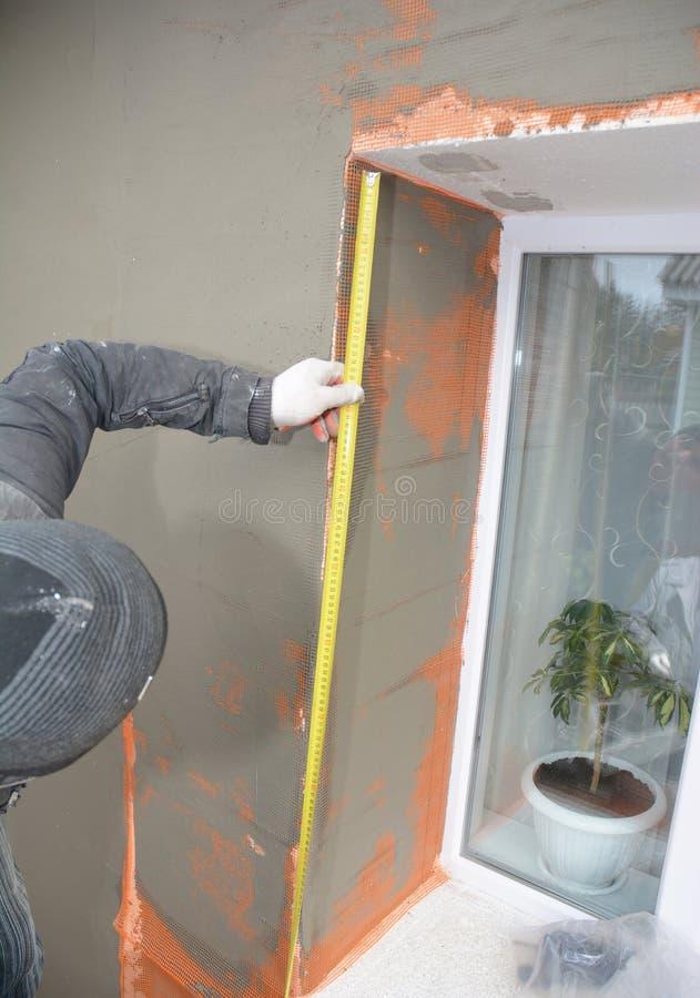 Entrepreneur de bâtiment mesurant plâtrant le mur avec la maille de fibre de verre, maille de plâtre après isolation rigide dans  photo stock