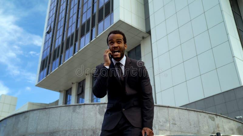 Entrepreneur de mulâtre criant dans la pression soumise à une contrainte et surchargée de téléphone de date-butoir photo libre de droits