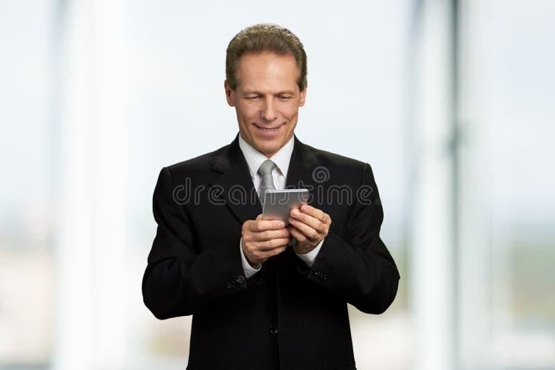 Entrepreneur de sourire heureux regardant le smartphone photo stock