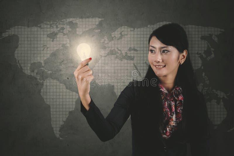 Entrepreneur féminin tenant une ampoule lumineuse images libres de droits