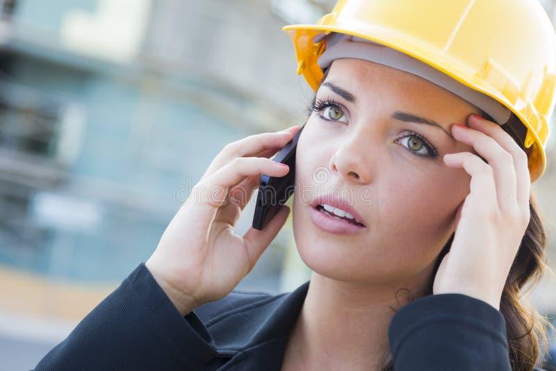 Entrepreneur femelle inquiété utilisant le casque antichoc sur le site utilisant le téléphone photographie stock