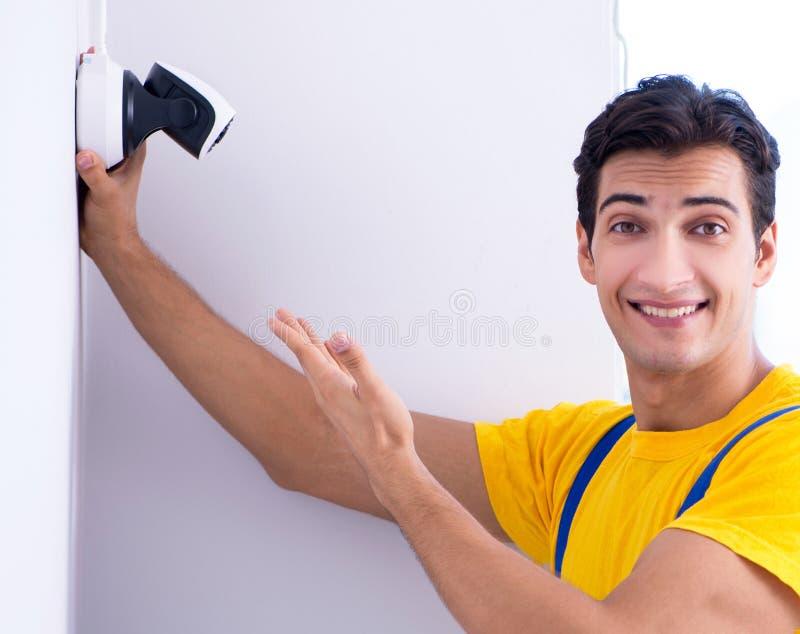 Entrepreneur installant des appareils-photo de t?l?vision en circuit ferm? de surveillance dans le bureau photo stock