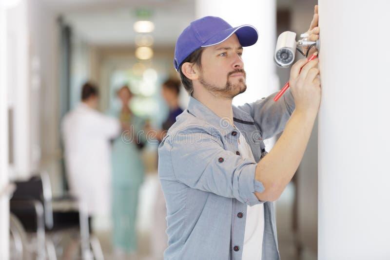 Entrepreneur installant la caméra de télévision en circuit fermé dans l'hôpital photo libre de droits