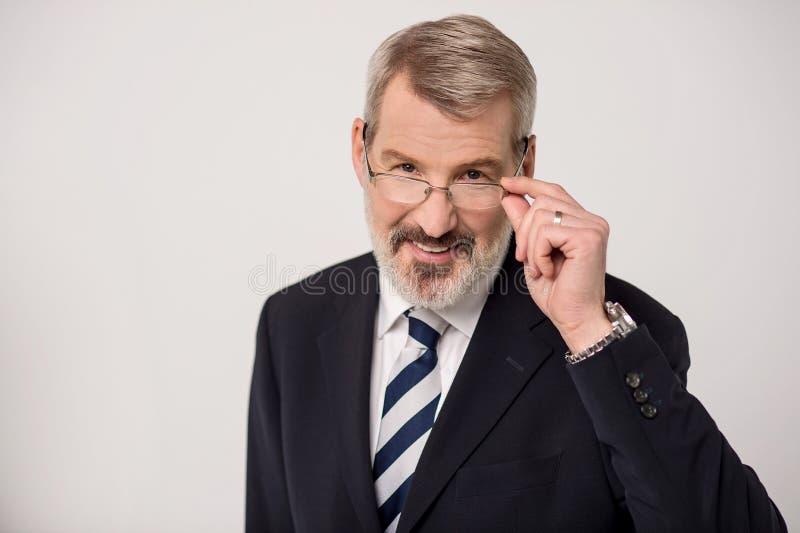 Entrepreneur masculin supérieur ajustant des lunettes images stock
