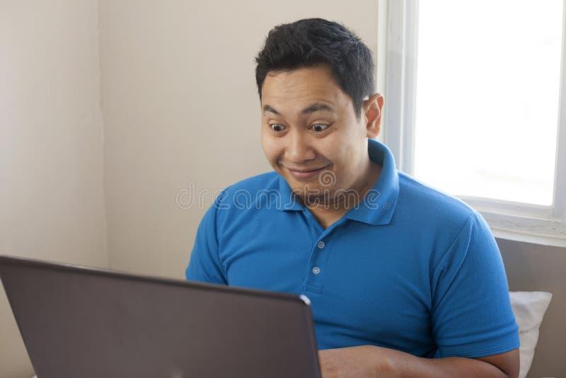 Entrepreneur masculin Working Online Business de maison, expression de sourire heureuse regardant l'ordinateur portable image stock