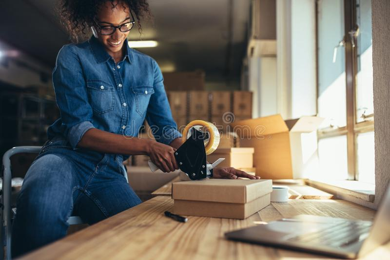 Entrepreneur packing parcel using tape dispenser stock images