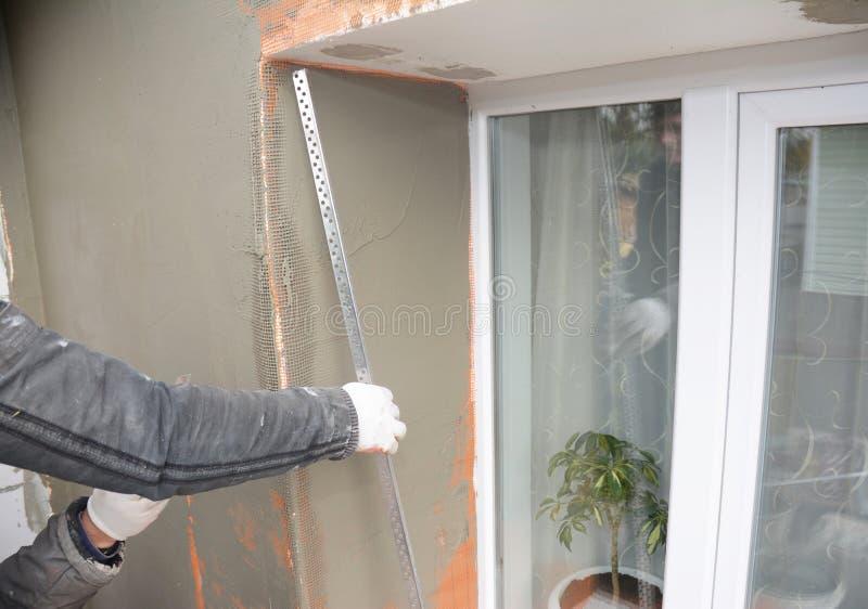 Entrepreneur plâtrant le mur avec le couteau de mastic, maille de fibre de verre, maille de plâtre après isolation rigide photo stock