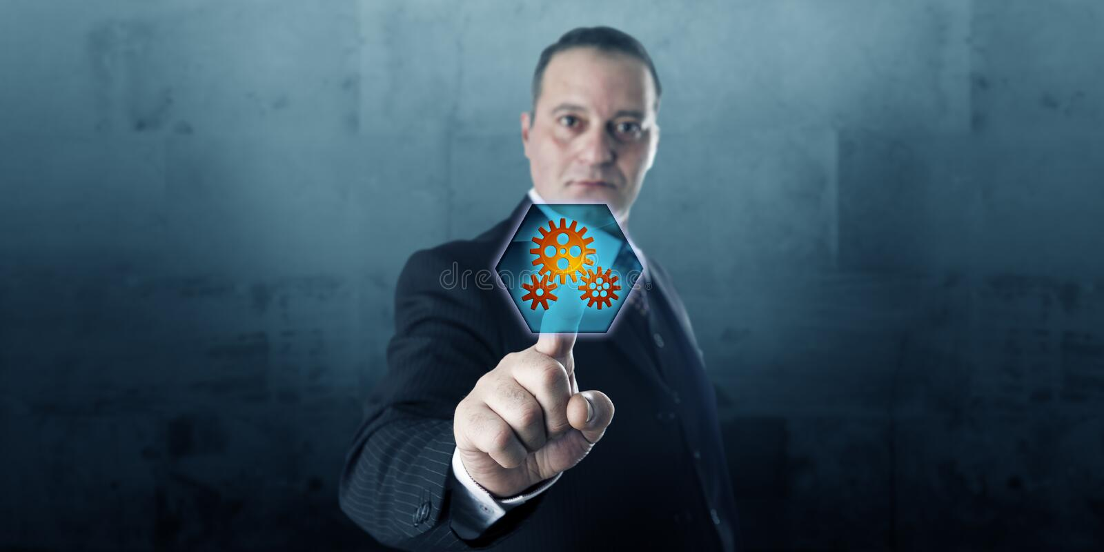 Entrepreneur Pressing Push Button With Cog Wheels. Male entrepreneur is pressing a hexagonal push button displaying three gear wheels. The virtual icon is royalty free stock images
