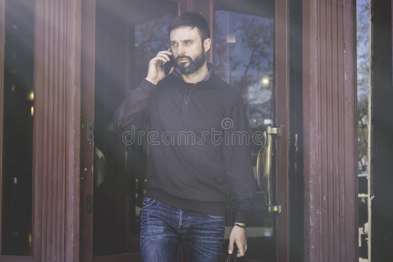 Entrepreneur professionnel occasionnel à l'aide du téléphone intelligent dehors Homme barbu en parlant à un téléphone portable photographie stock