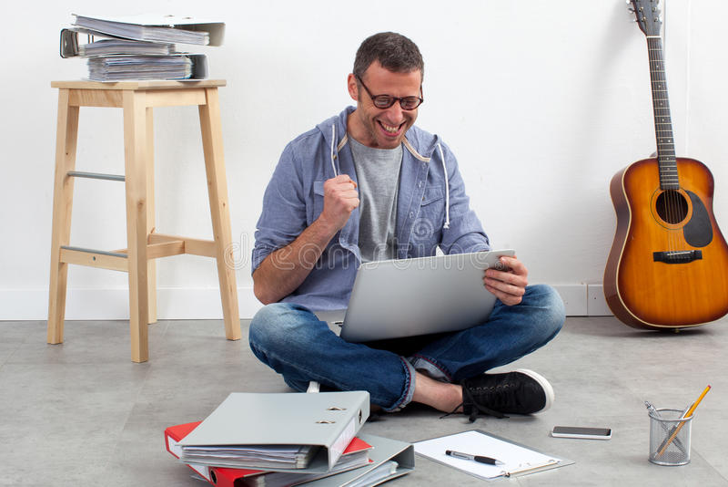 Entrepreneur réussi s'asseyant sur le plancher pour détendre et travailler photographie stock