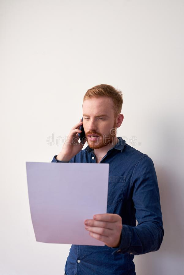 Entrepreneur reading important document. Businessman reading important document when talking on phone with colleague stock photography