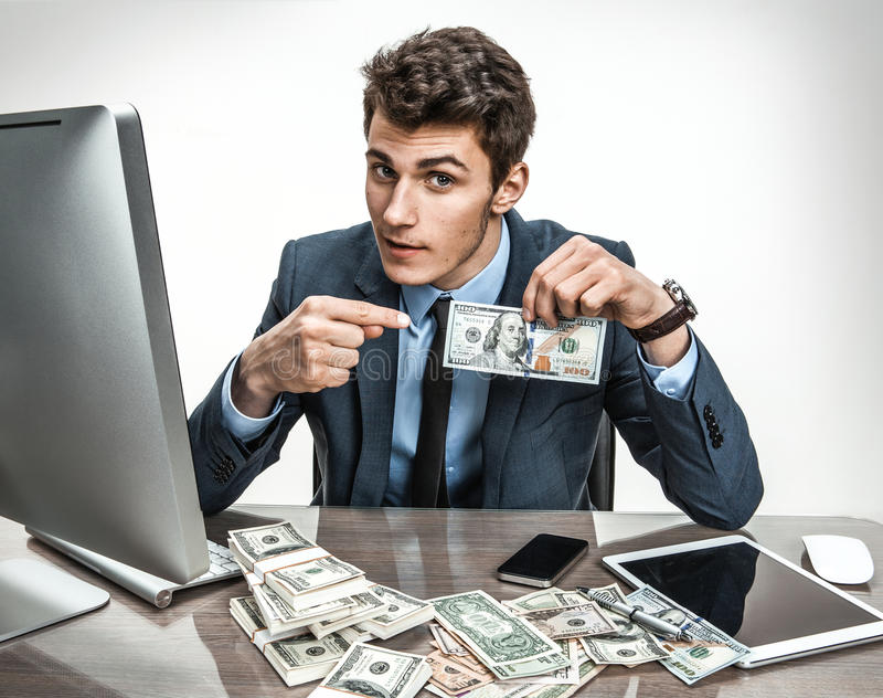 Entrepreneur showing his motivation earnings, profit, income, gain, benefit, margin. Modern businessman at his desk with computer and a lot of money royalty free stock images