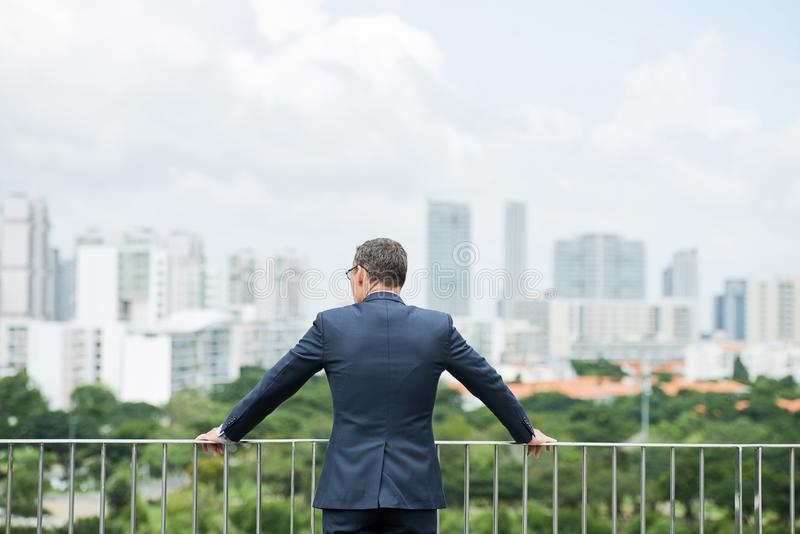 Enjoying city view. Entrepreneur standing on roof of his office and enjoying city view royalty free stock photo