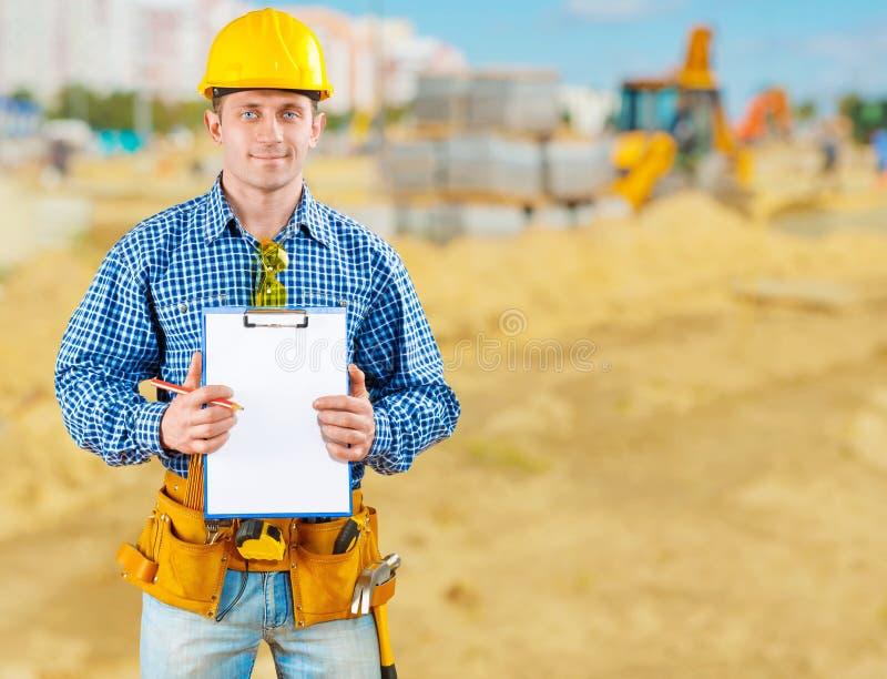Entrepreneur sur la construction de routes avec le presse-papiers image stock