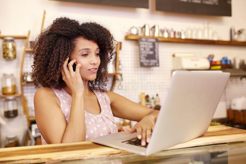Entrepreneur sur le téléphone et l'ordinateur portable de dactylographie images stock