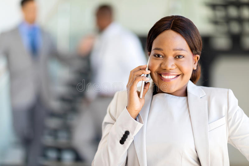 Entrepreneur talking cell phone. Beautiful young african entrepreneur talking on cell phone royalty free stock photo