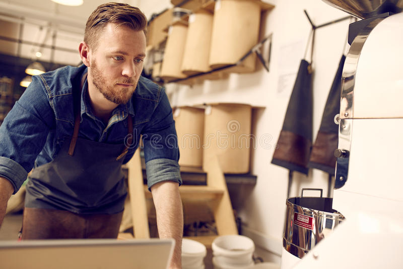 Entrepreneur travaillant dans son roastery ordonné et moderne de café photos libres de droits