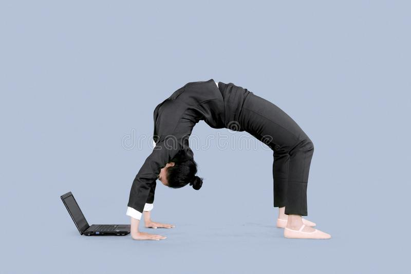 Entrepreneur uses a laptop with back bend pose royalty free stock photo