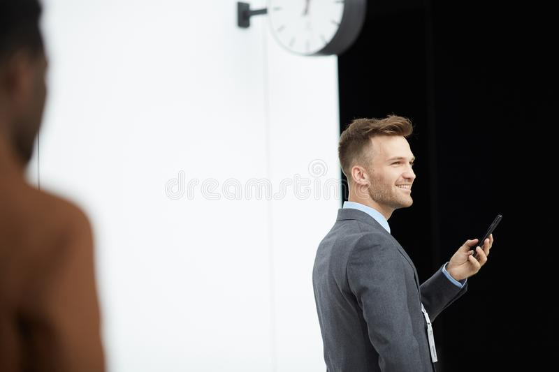 Entrepreneur in waiting area. Positive handsome entrepreneur in suit standing in waiting area with clock and checking smartphone royalty free stock photo