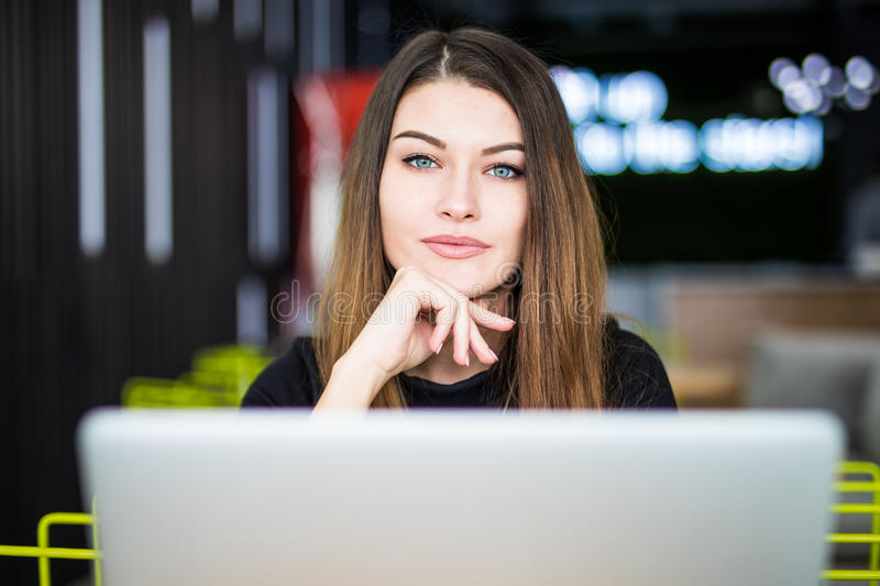 Entrepreneur woman working with a laptop in a coffee shop or hub smart space stock photography