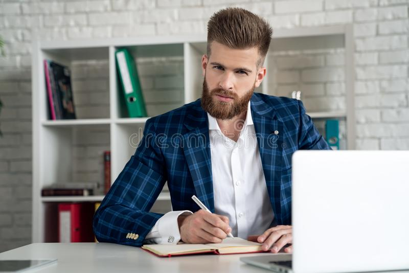 Entrepreneur writing notes sitting at his desk. Young man making business plans with papers and computers on his desk royalty free stock image