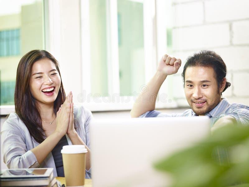Entrepreneurs asiatiques célébrant le succès et l'accomplissement dans le bureau image stock