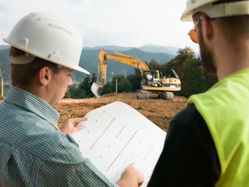 Entrepreneurs lisant des plans de construction images stock