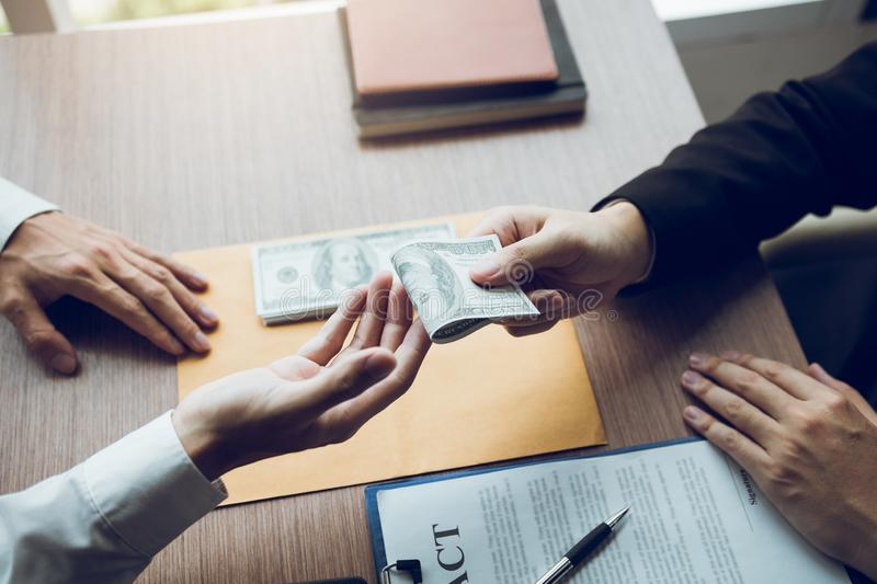 Entrepreneurs are receiving money that is a bribe of their partners with both of whom are corrupt in the company room.  royalty free stock images