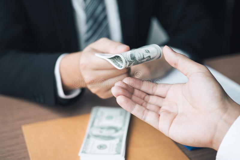 Entrepreneurs are receiving money that is a bribe of their partners with both of whom are corrupt in the company room.  royalty free stock photography
