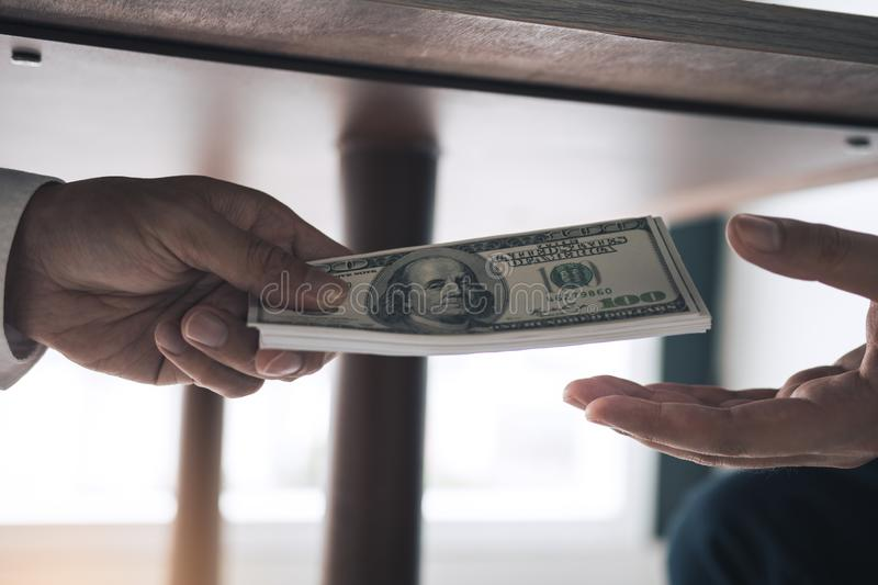 Entrepreneurs are receiving money under the desk that is a bribe of their partners with both of whom are corrupt in the company. Room stock image
