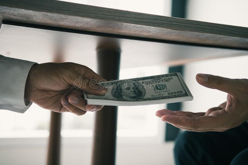 Entrepreneurs are receiving money under the desk that is a bribe of their partners with both of whom are corrupt in the company. Room royalty free stock images