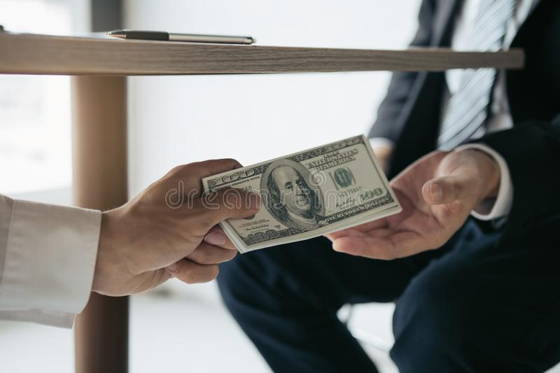 Entrepreneurs are receiving money under the desk that is a bribe of their partners with both of whom are corrupt in the company. Room stock photos