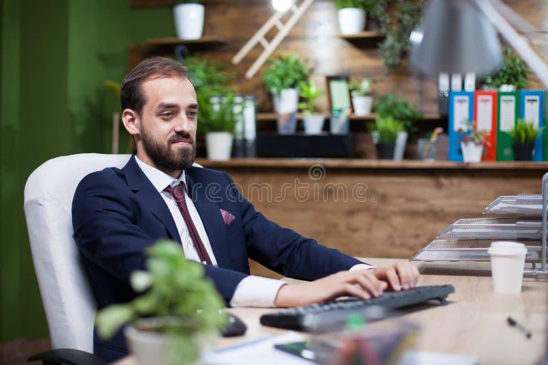 Entreprenur novo seguro que trabalha em seu computador vestido no terno de negócio imagem de stock royalty free