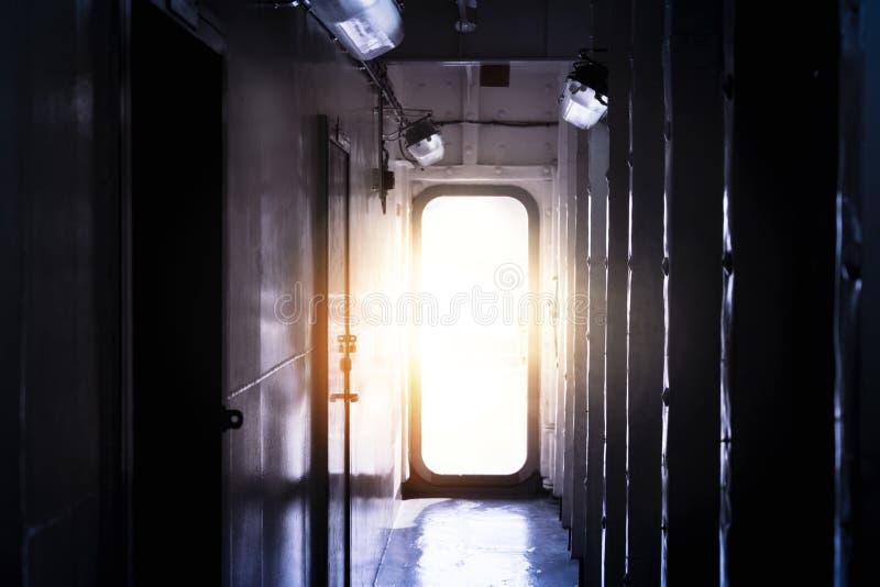 Entrer léger par la porte ouverte à une salle vide sombre image stock