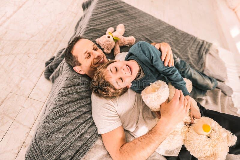 Entretenant l'homme étreignant affectueusement son fils tout en se reposant sur un matelas image libre de droits