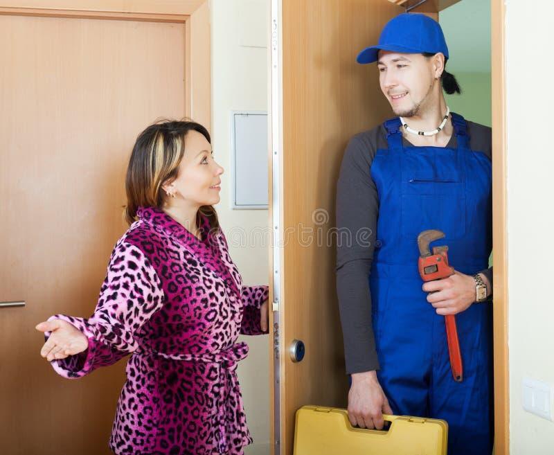 Entretenez le travailleur dans l'uniforme est venu à la femme au foyer photo libre de droits