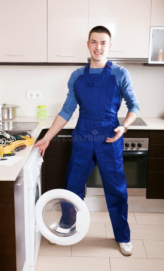 Entretenez le travailleur réparant la machine à laver images libres de droits