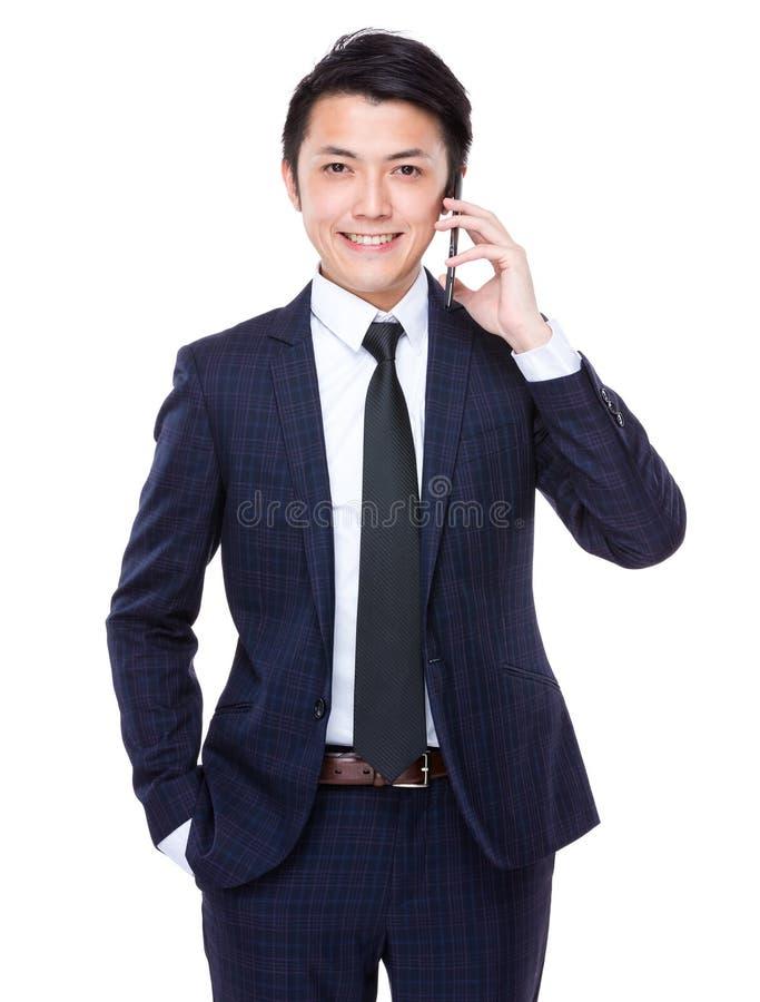 Entretien asiatique d'homme d'affaires au téléphone portable photo stock