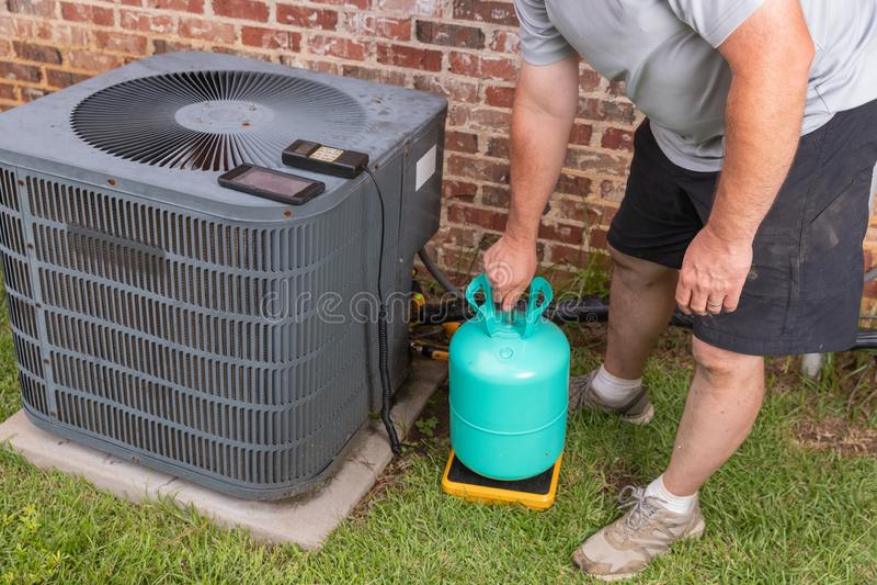 Entretien avec un climatiseur avec un technicien ajoutant du réfrigérateur image libre de droits