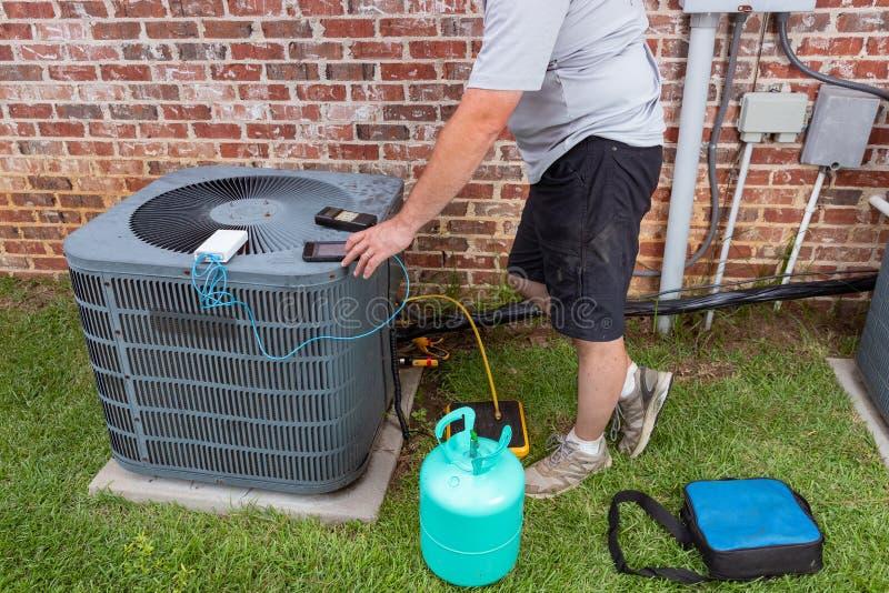 Entretien avec un climatiseur avec un technicien ajoutant du réfrigérateur photographie stock libre de droits