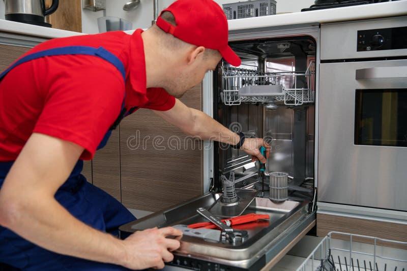Entretien d'appareil ménager - dépanneur réparant le lave-vaisselle dans la cuisine photographie stock libre de droits