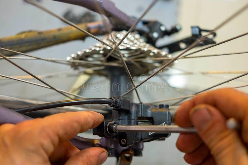 Entretien de bicyclette réparant les freins à disque sur un vélo de montagne photos stock