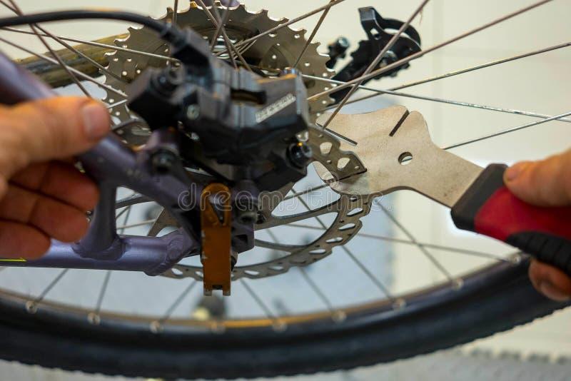 Entretien de bicyclette réparant les freins à disque sur un vélo de montagne photos libres de droits