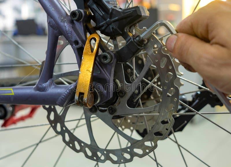 Entretien de bicyclette réparant les freins à disque sur un vélo de montagne images stock