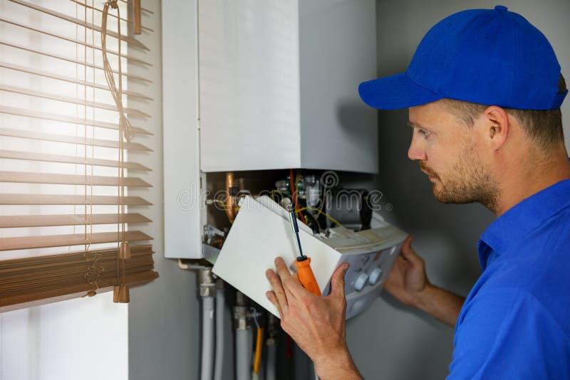Entretien et ingénieur de service des réparations travaillant avec la chaudière de chauffage au gaz de maison images libres de droits