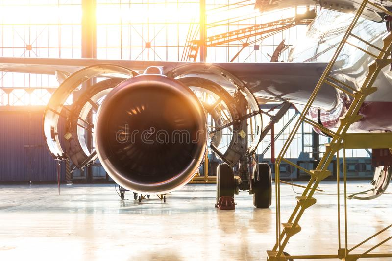 Entretien ouvert de jet de moteur d'avion de capot dans les escaliers de hangar, avec la fusée légère lumineuse à la porte photo stock