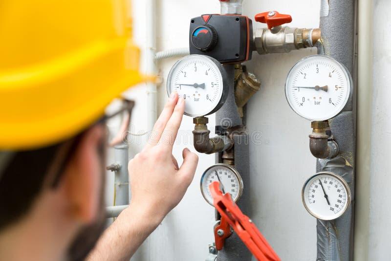 Entretien - technicien vérifiant des mètres de pression de chauffage photo libre de droits